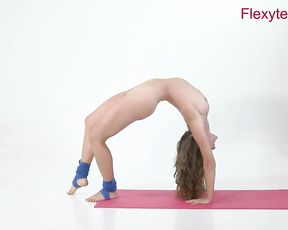 Flexible nude gymnast does naked yoga at the studio