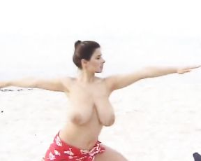 Nude MILF with big tits doing naked yoga exercises in public