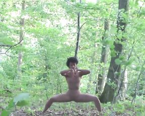 Hot yoga girl in sexy bodysuit dances in the wood