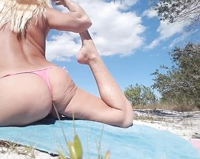 Nearly naked MILF does hot yoga on the public beach