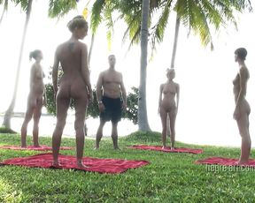 A group of nude flexible girls does naked yoga workout with the trainer in a public place