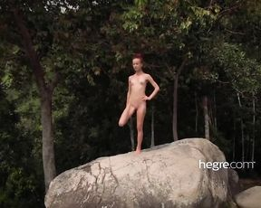 Naked skinny woman does flexible nude yoga exercises in the wilderness