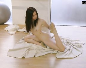 Flexible naked ballerina warms up in nude ballet class