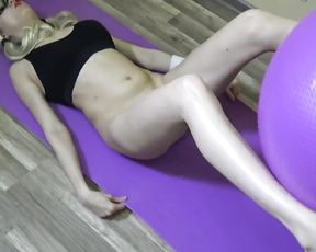Naked girl fucks herself with a dildo on yoga ball in the gym